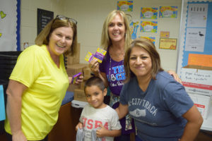 Junior Forum Fill the Bus Chair Linda Simonson and The Locker founder Karen Crosby help Annie Purl Kindergärtner Jesse Gonzales collect his first school supplies with mom Sandra.