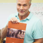 Teacher/editor Ed Straka holds up his cover art.