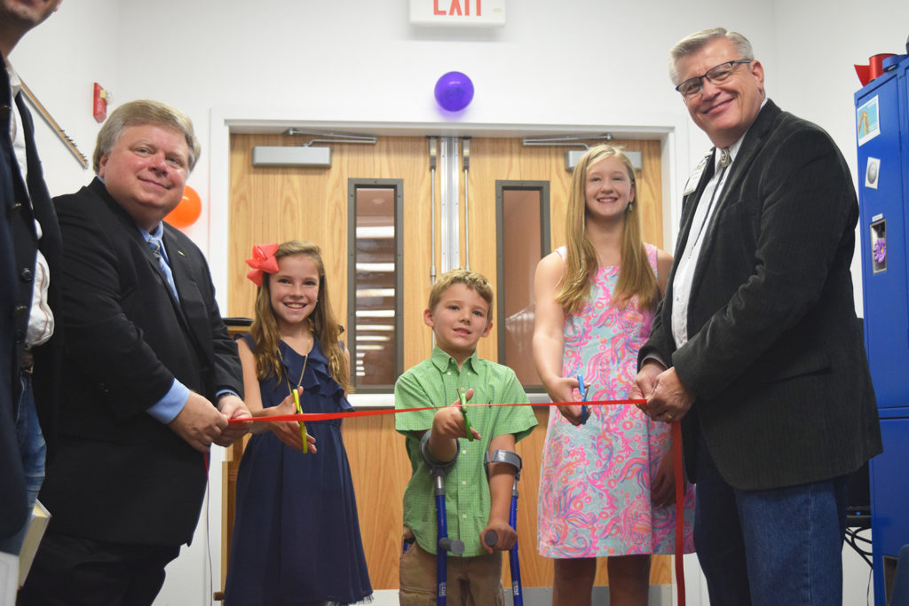 "Mayor Dale Ross, Olivia (5th grade), ""Super"" Cooper (1st grade), and Catherine (8th grade) and Pastor John Davenport prepare to cut the ceremonial ribbon. ""This is our future."""
