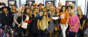 Style students at the Salon Professional Academy present a check to Karen Crosby of The Locker (front, holding check) with Academy owner Tuesday Wilson (in UT jersey)